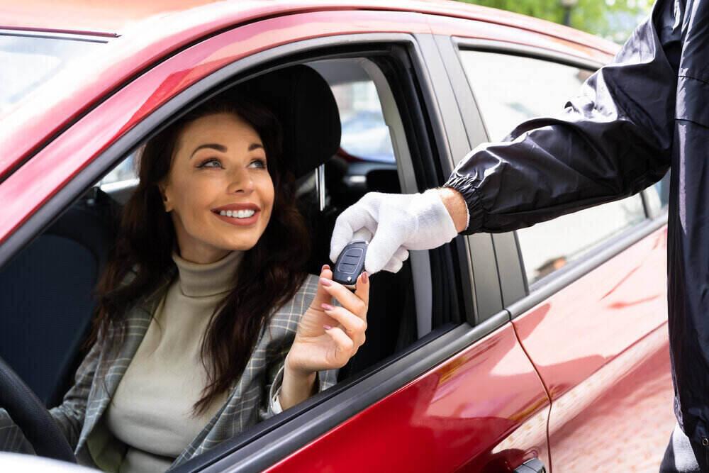 araç kiralama vale hizmeti, kırmızı arabada araç anahtarını teslim alan kadın sürücü