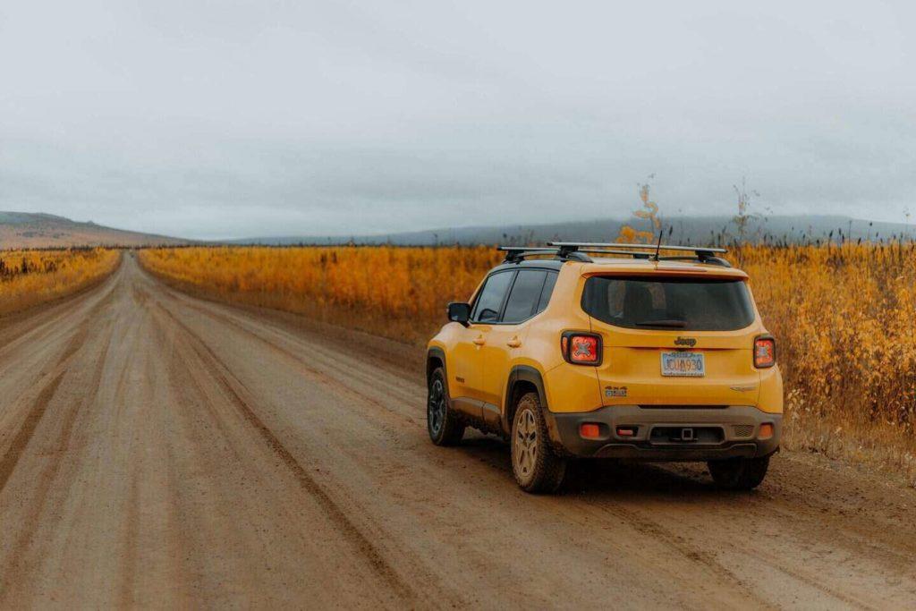 aylık araç kiralama fiyatları ne kadar? tarla yolunda duran sarı renkli suv araç