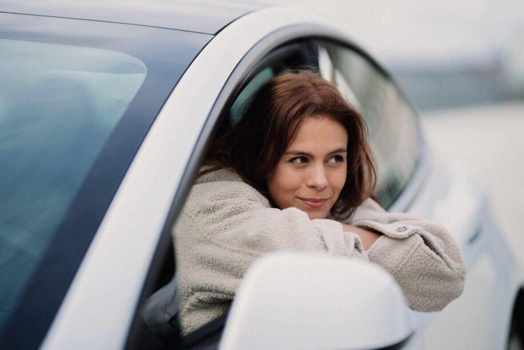 günlük araba kiralama fiyatları ne kadar? kadın sürücü araç kapısından dışarı bakıyor